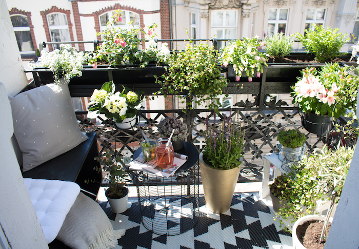 petit balcon, amenagement terrasse minuscule, assise en bois, coussins et couverture gris, tapis noir et blanc, pots de fleurs, plantes vertes, table en poubelle retournée