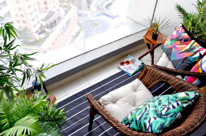 balcon deco terrasse petite, carrelage beige, tapis noir à petites rayures blanches, fauteuils en rotin, plantes vertes exotiques