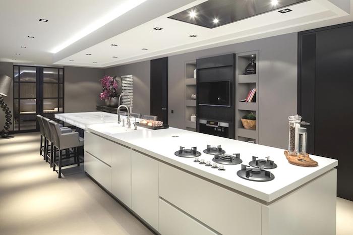 cuisine semi ouverte, carrelage de sol beige, murs de cuisine peints en taupe, grande lampe sur pied à motif industriel