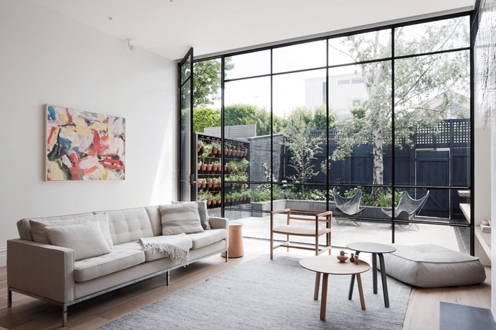 salon inspiration scandinave, tapis gris, canapé blanc, tables gigognes en bois, pouf gris et verrière qui donne sur un jardin