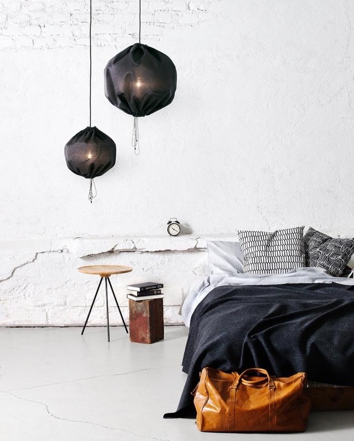 deco esprit scandinave dans la chambre à coucher, mur blanc défraichi, suspensions noires, linge de lit gris, blanc et noir, table de nuit en bois et metal