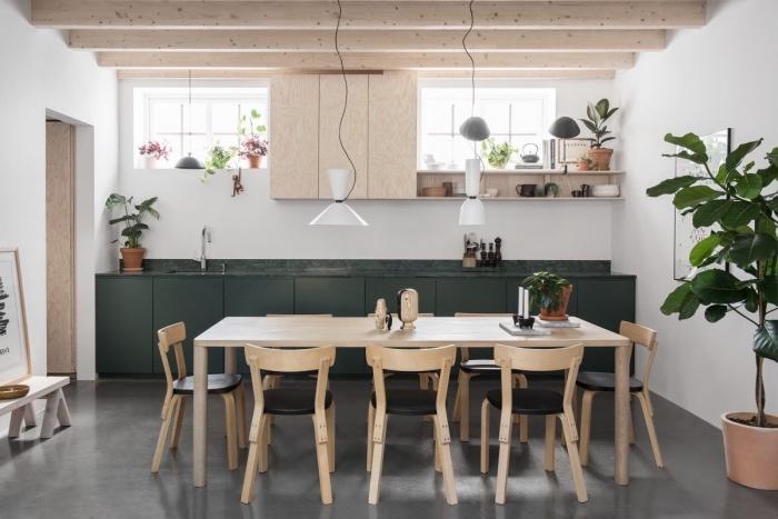 meuble scandinave, table en bois massive, chaises bois et cuir noir, façade cuisine vert foncé et poutres apparentes, deco de plantes vertes
