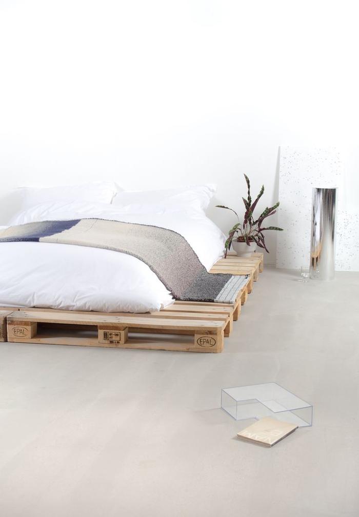 un espace natutel et zen avec un sommier en palette posé au sol, bordé d'un espace tablette