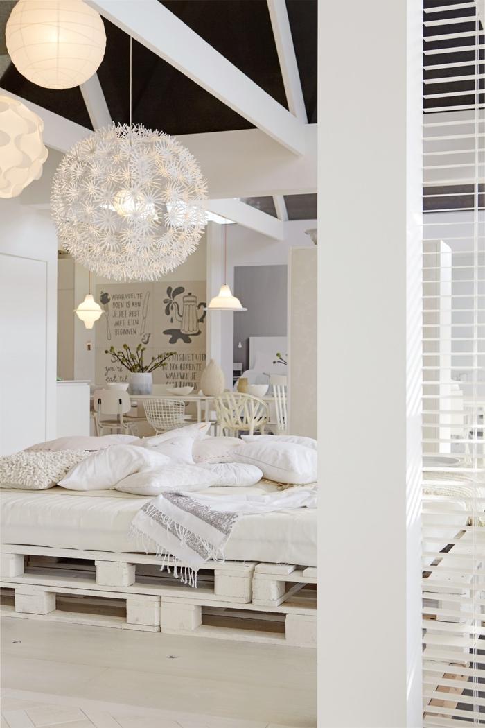 un salon spacieux tout en blanc pour une ambiance relaxante équipé d'un grand sommier en palette
