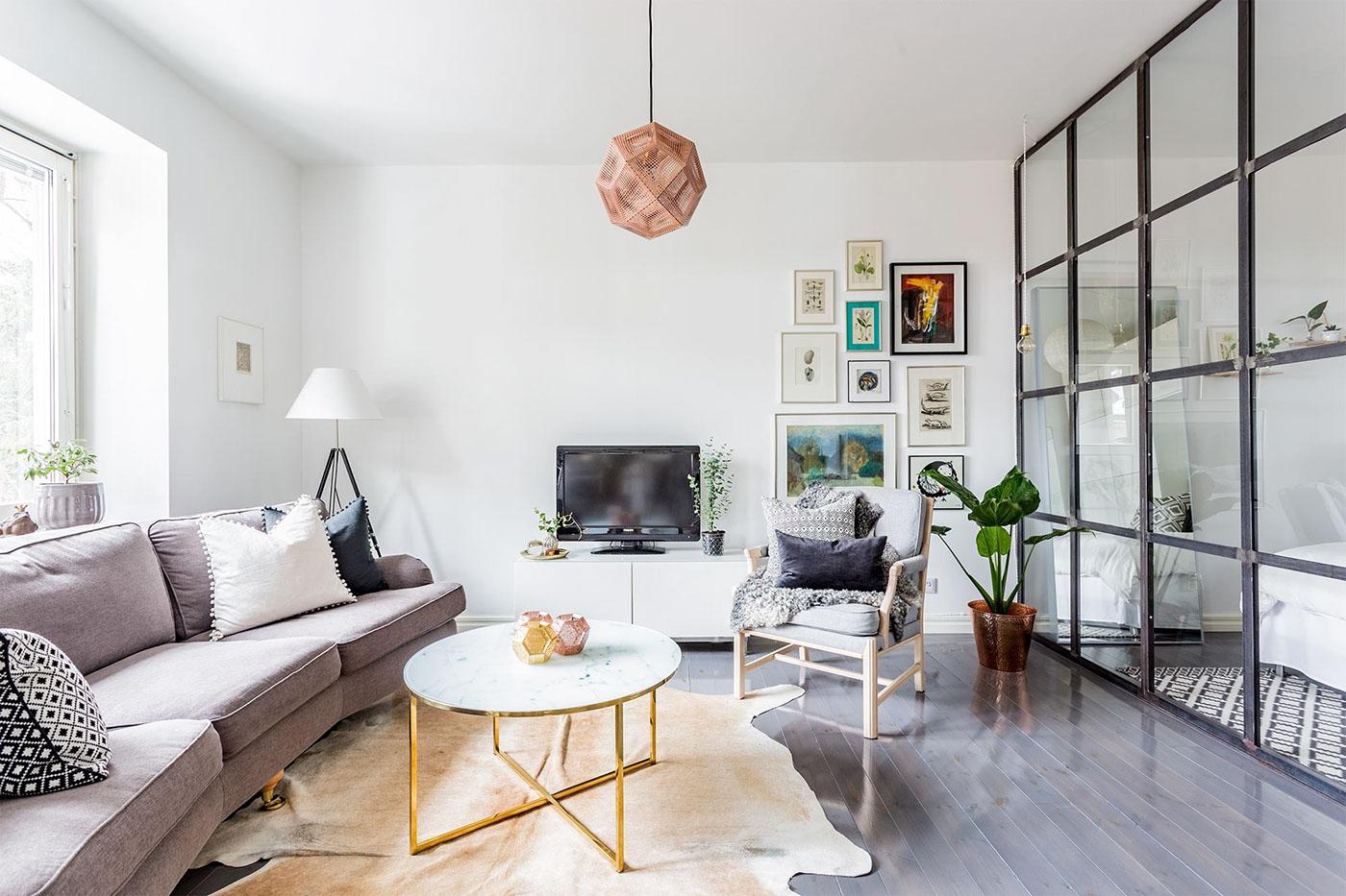 modele de salon cocooning, canapé mauve, tapis de peau animale, chaise en bois, table basse plateau en marbre, murs de cadres decoratifs