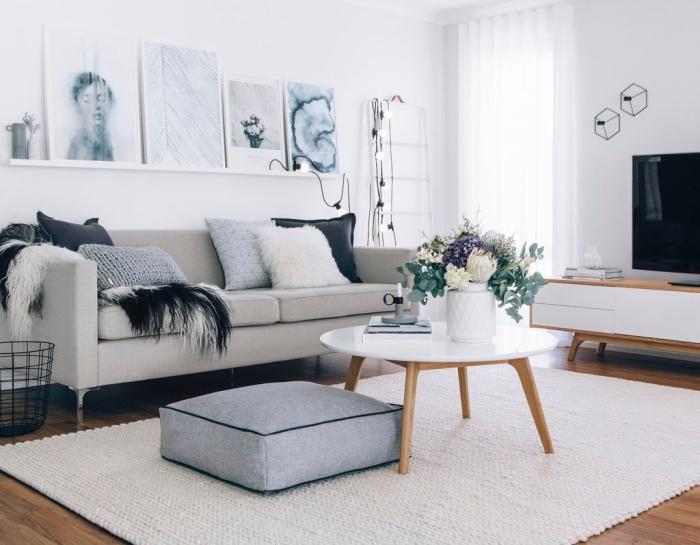 salon scandinave à deco cocooning, table basse et parquet bois, tapis blanc tissé, assise grise, canapé gris et coussins décoratifs, guirlande lumineuse