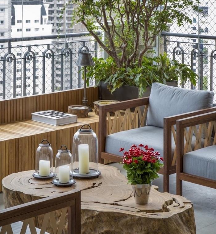 aménager une terrasse eb bois, canapé, table en bois brut, fauteuils en bois, coussins gris, lanternes avec des bougies