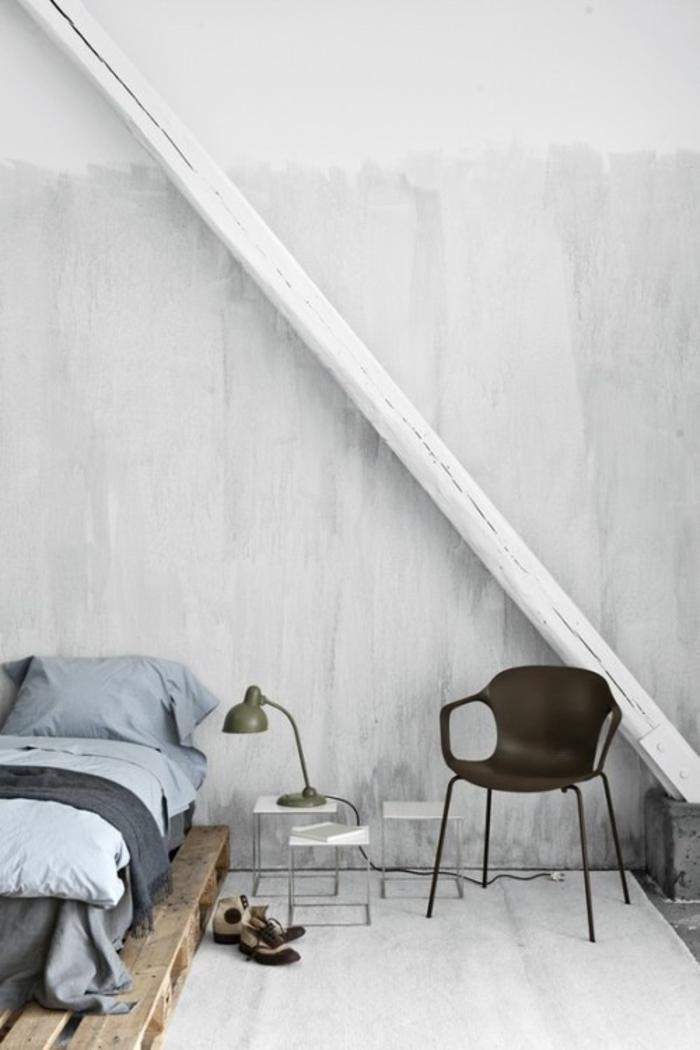 une chambre à coucher de style industrielle en blanc et gris équipée d'un sommier en palette au design minimaliste bordé d'une petite table de chevet en acier chromé