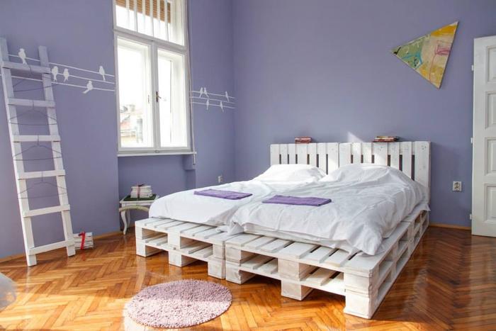 une chambre à coucher douce et féminine en violet avec un sommier en palette peinte en blanc et sa tête assortie