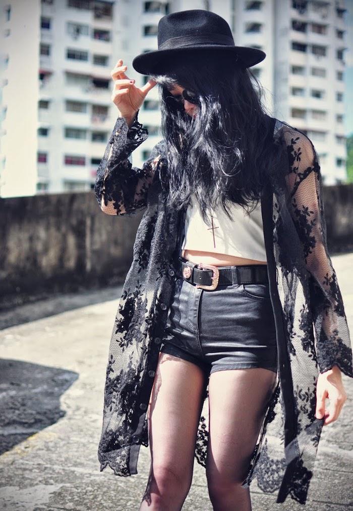 coupe de cheveux longs coloration noire, top blanc avec shorts noirs, gilet long à motifs floraux