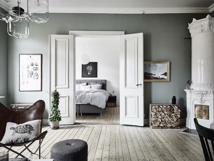 chambre à coucher ouverte sur salon, parquet gris clair, lit gris avec linge de lit blanc cassé, chaise cuir, cheminée blanche, intérieur rustique
