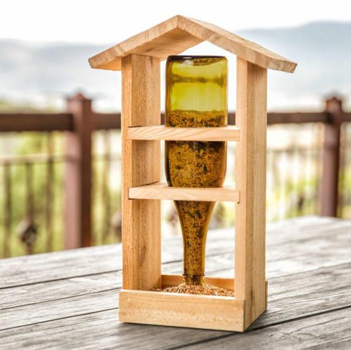 mangeoire oiseaux, encadrement-de-bois-et-boîte-remplie-de-graines-renversée