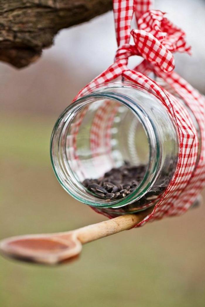 mangeoire à oiseaux, bocal de verre plein de graines de tournesol, ruban et cuillère en bois