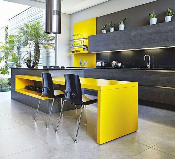 ilot central en jaune, meubles de cuisine en gris foncé, pot à fleur blanc, comptoir noir avec évier onyx