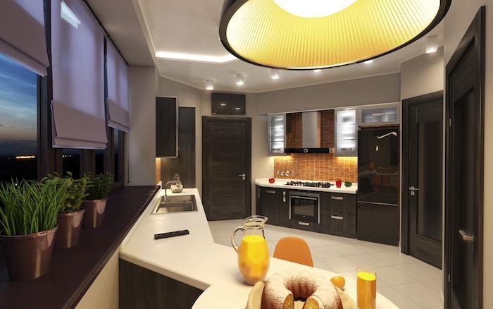 cuisine aménagée, éclairage sous meubles jaune, meubles de cuisine en noir avec poignées métalliques