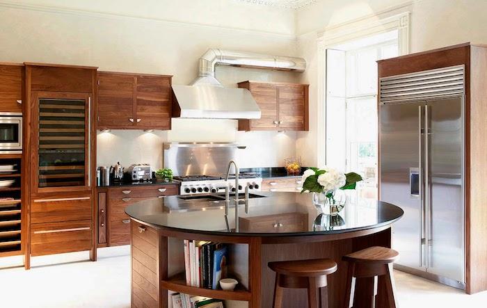 cuisine équipée, plafond et sol blanc, meubles en bois foncé, ilot central rond en bois marron et comptoir noir