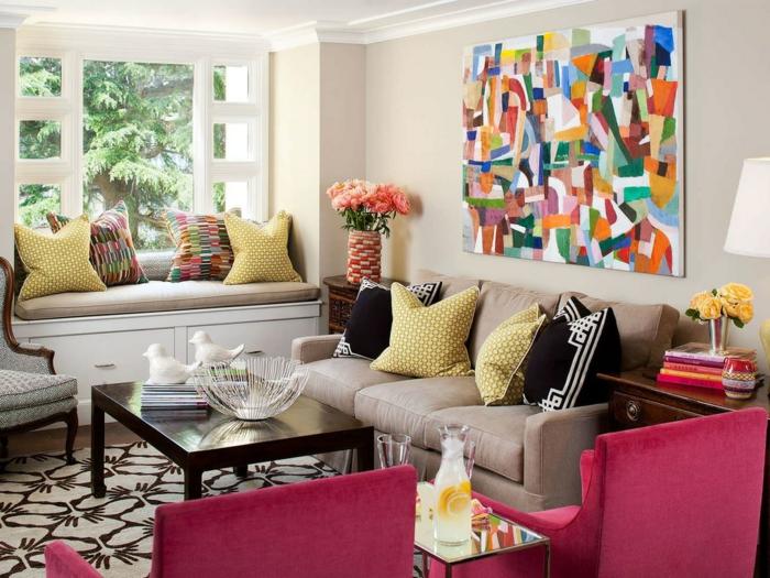 meuble gris, fauteuils roses, tapis à motifs originaux, coussins déco, tableau abstraitn table en bois foncé