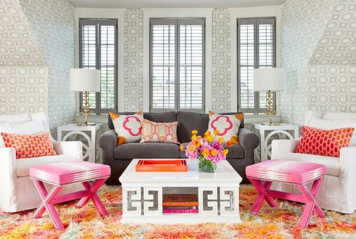 meuble gris, tapis orange, table blanche rectangulaire, tabourets roses, coussins bariolés