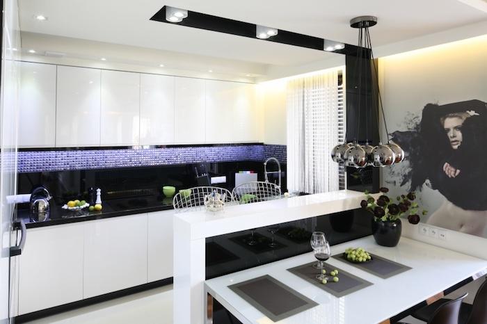 cuisine aménagée, meubles de cuisine blanc sans poignées, carrelage mosaïque violet et noir