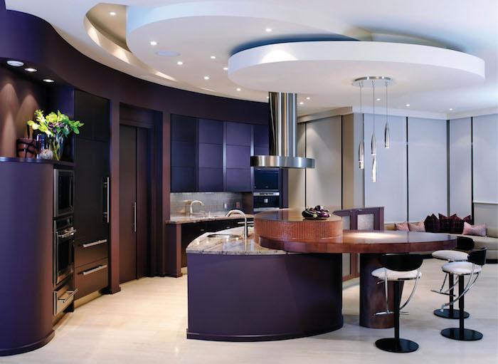 cuisine semi ouverte, ilot central violet avec comptoir en marbre et évier en onyx, tabourets de bar blanc et noir