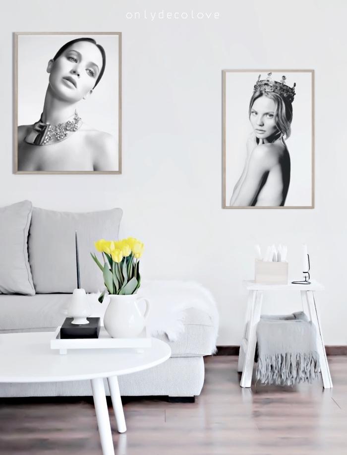 meubles scandinaves dans un salon gris et blanc, canapé blanc, coussins gris, parquet marron, table basse blanche, deco de photos en noir et blanc