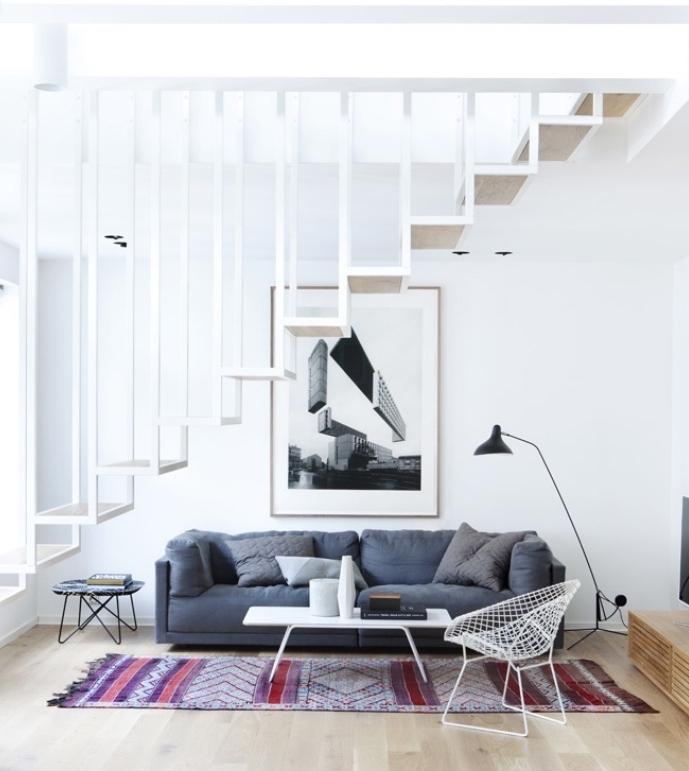 idée de salon scandinave avec canapé gris et tapis oriental, table basse blanche, chaise en métal, escalier design blanc
