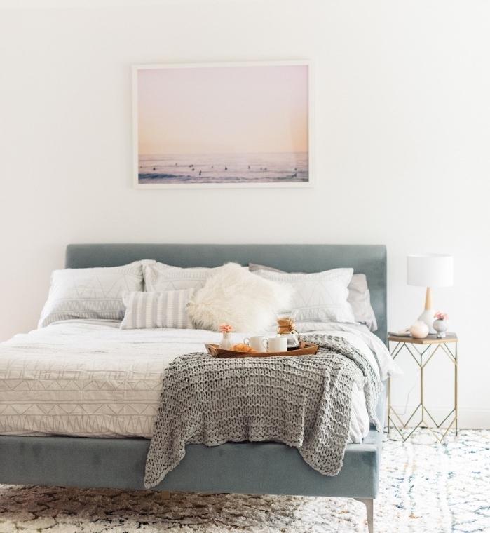 meuble scandinave, grand lit bleu gris, linge de lit blanc, couverture grise, deco photo paysage bord de mer, tapis blanc à motifs géométriques