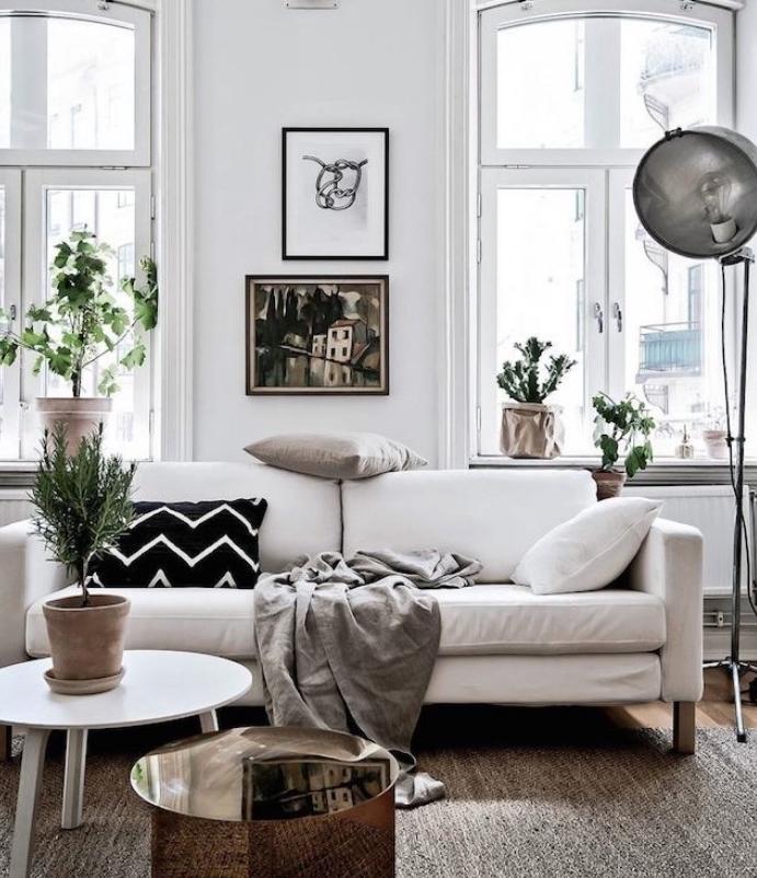 deco esprit scandinave avec canapé blanc, couverture gris et coussins décoratifs noir, blanc et gris, table basse blanche, mur blanc, deco de plantes vertes
