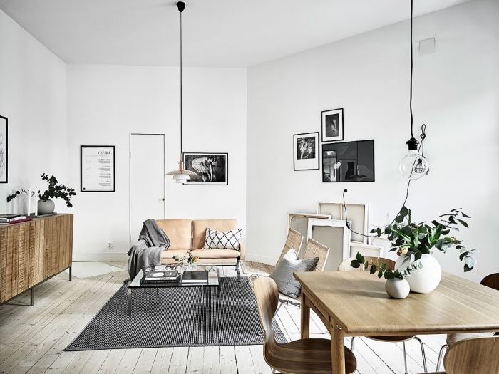 meubles scandinaves dans un salon, canapé eux places en cuir, tapis noir et blanc, table et chaises bois dans un coin salle à manger, parquet gris clair, deco murale graphique