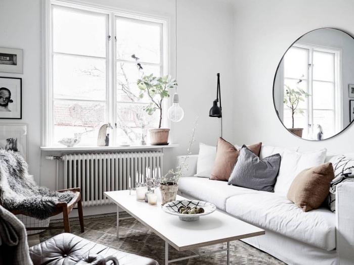 meubles scandinaves dans un salon moderne, canapé blanc, coussins gris et marron, table basse blanche, tapis gris à formes géométriques, chaise peau animal grise, intérieur blanc, miroir rond