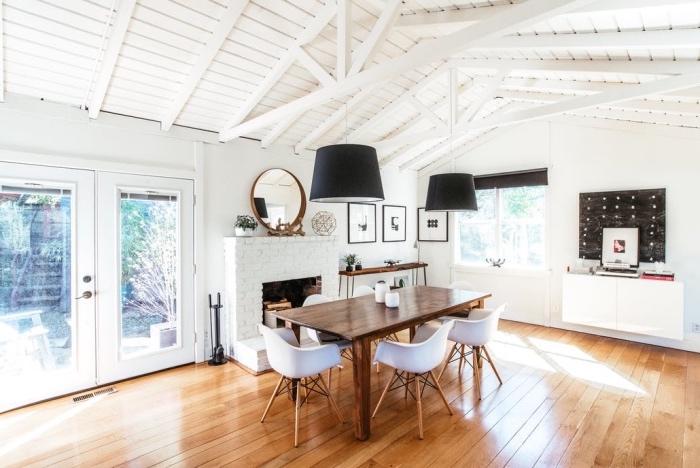 idée de meuble scandinave, parquet clair, table bois massif et chaises scandinaves, suspensions noires, cheminée en briques, ossature bois blanc, poutres apaprentes
