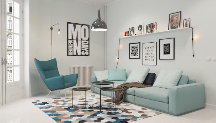 mobilier scandinave en canapé bleu pastel et chaise bleu canard, tapis à motifs géométriques, tables basses noires, étagère blanche, rangement photos, suspension grise design