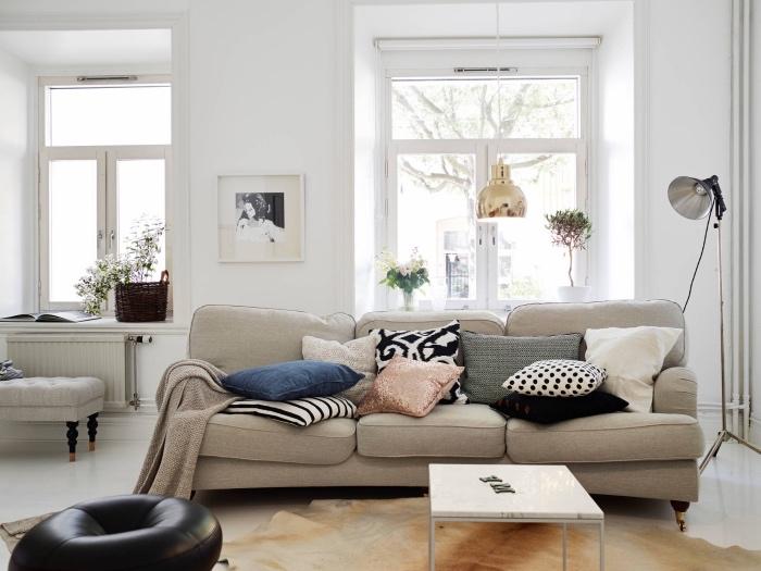 mobilier scandinave dans un salon moderne nordique avec canapé gris, tapis peau animal, peinture murale blanche, assise noire en cuir, coussins colorés, suspension dorée