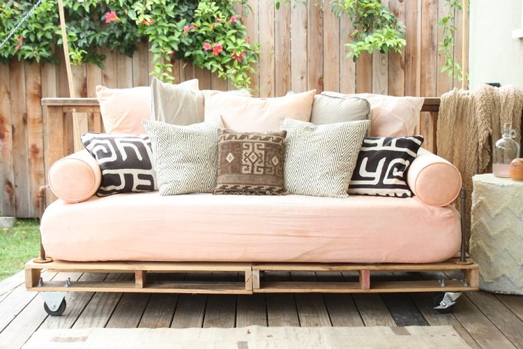 modèle de canapé en palette, constitué de deux palettes assemblées avec des roulettes, matelas saumon et coussins rose, blanc, noir et marron, déco avec de la récup exterieur