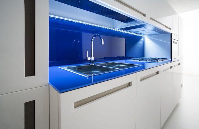 idee deco cuisine, meubles blancs de cuisine sans poignées, éclairage néon bleu sous meubles