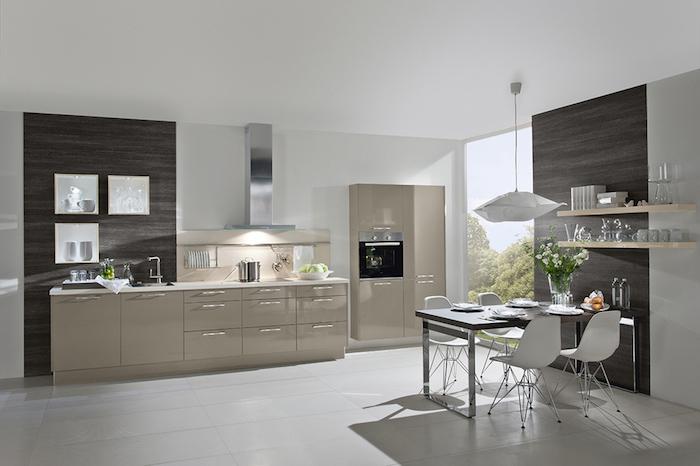 cuisine équipée, meubles beige avec poignées métalliques, table à manger noir avec chaises blanches