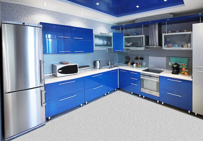 cuisine semi ouverte, plafond en blanc et bleu avec éclairage LED, meubles de cuisine bleus avec poignées gris