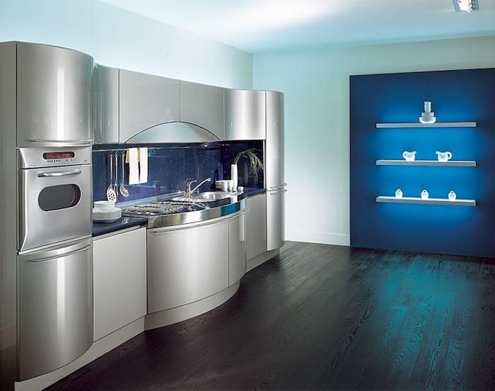 cuisine aménagée, plafond blanc et sol en bois foncé, meubles de cuisines en gris métal, étagère murale avec éclairage neon