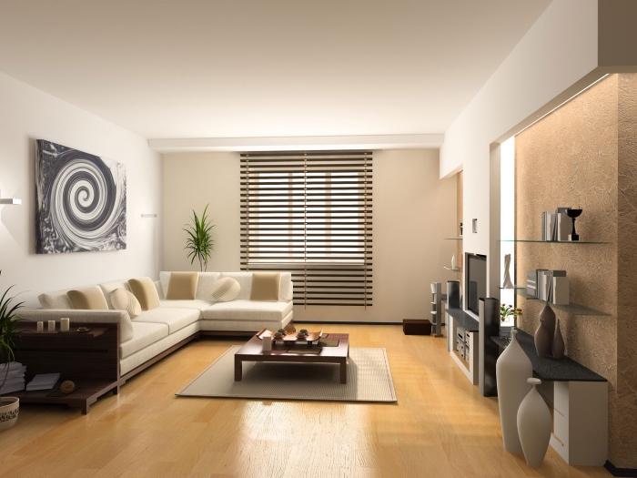 mur accent beige, plafond et murs blancs, parquet bois clair, canapé blanc cassé avec des coussins beiges, étagères noires
