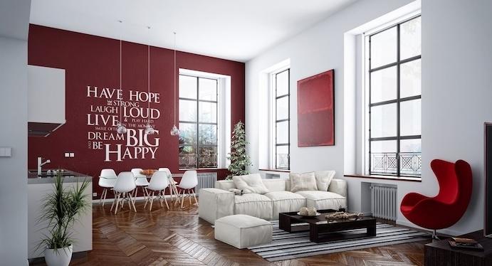 mur d accent couleur bordeau dans une cuisine salle à manger ouverte sur un salon, coin repas avec table en verre et chaises scandinaves, façade cuisine blanche, salon avec canapé et tabouret blanc, table basse marron et fauteuil rouge