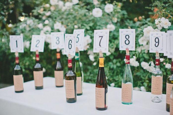 bouteilles de vin personnalisés avec étiquettes invités collées dessus et nombre de table dans une fente du bouchon de liège, diy mariage plan de table