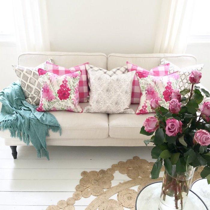 tendance deco, salon aux murs et plancher en blanc, bouquet de rose en vase verre, coussins à motifs floraux rose et blanc