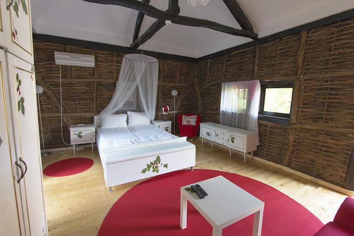 deco chambre, tapis rond en framboise, lit à baldaquin, garde-robe blanche à décoration florale, chaise en tissu rouge