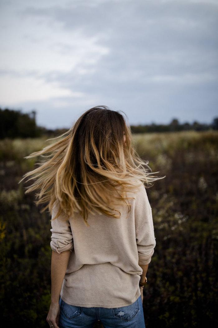 balayage sur cheveux chatain, blouse beige et pantalon en denim modèle femme, coiffure avec racines foncées