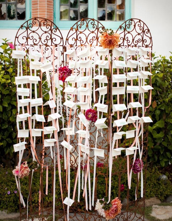 plan de table mariage diy avec des portes, grille métallique style baroque, décoration de rubans blancs et rose, fleurs épanouies et étiquettes blanches