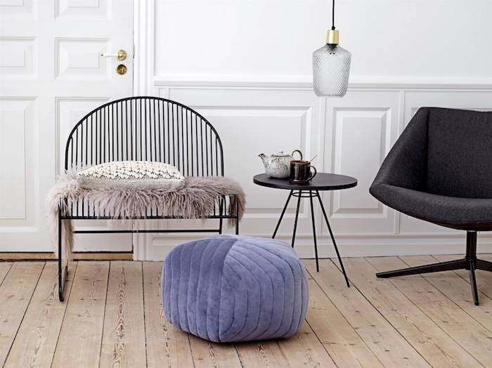 deco cocooning scandinave, parquet clair, chaise metallique noire avec pouf violet, jeté de fourrure, fauteuil gris anthracite et mur blanc