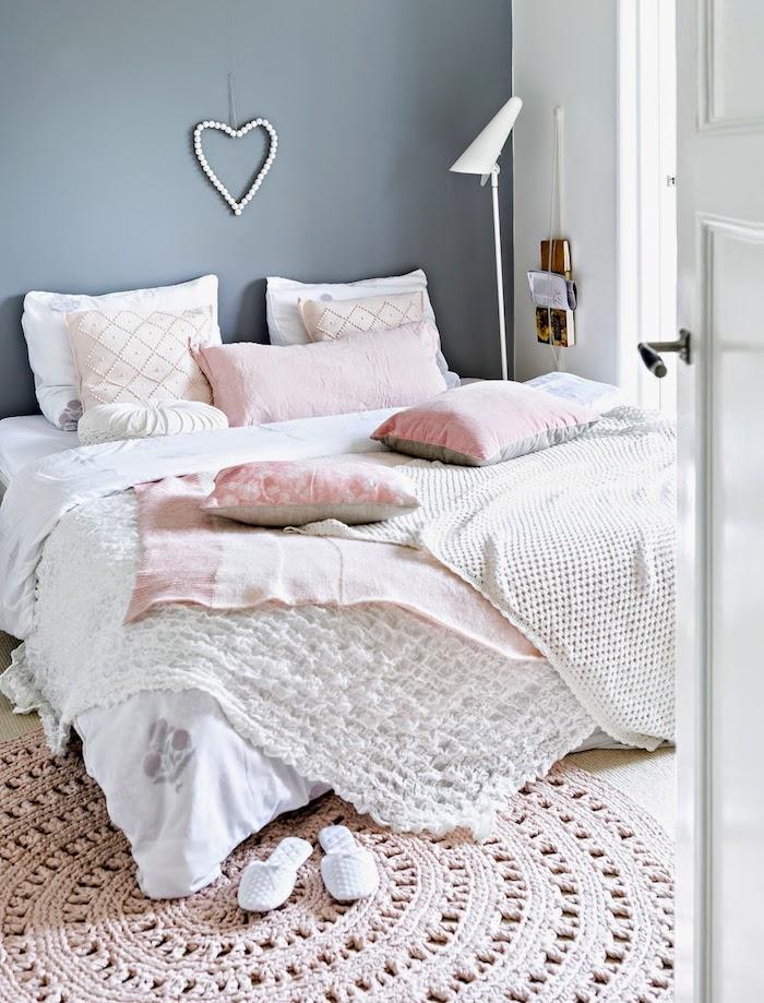 chambre à coucher romantique, grand lit couvert avec plaid blanc et coussins décoratifs en rose pale