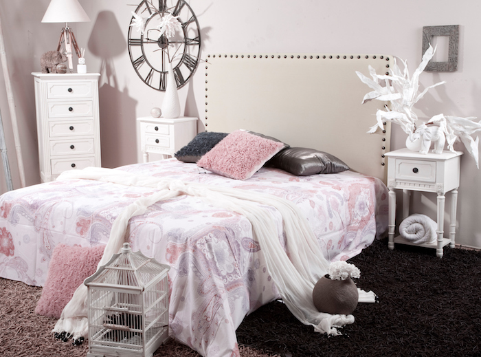 deco maison, voiles blanches sur le lit, couverture de lit à motifs dentelle et fleurs rose, lampe de chevet blanche