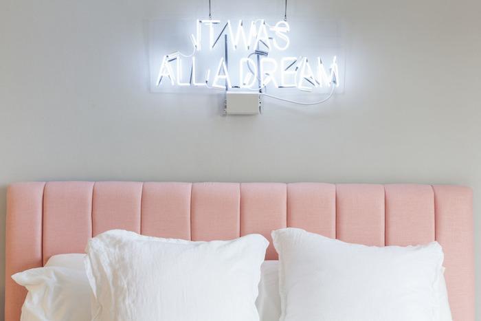décoration chambre à coucher aux murs gris clair, tête de lit en rose, lettres lumineux au-dessus de lit