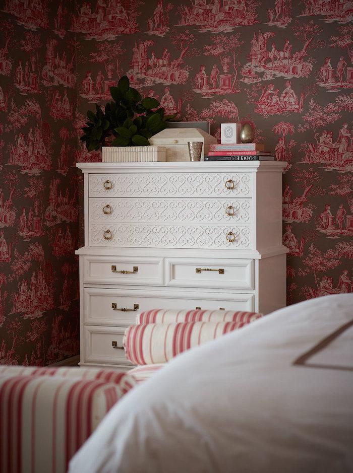 objet deco, armoire blanche à poignées dorées, accessoires décoratifs feuilles vertes, papier peint marron et rose foncé